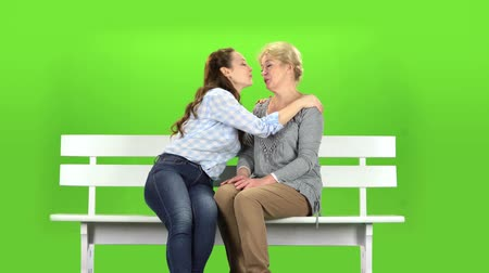 tópicos : Daughter kisses her mother on the cheek. Green screen