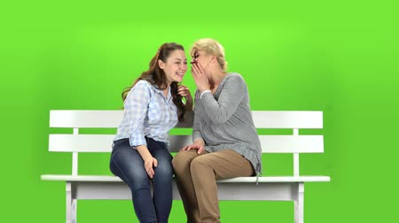 konuları : Daughter and mom are sitting on a bench. Green screen
