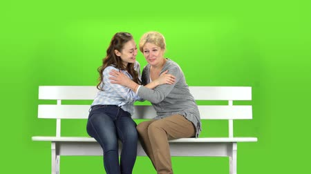 konuları : Native to embrace, they are sitting on a white bench. Green screen Stok Video