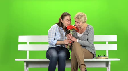 benches : Girl with her mother is sniffing a bouquet of flowers. Green screen Stock Footage