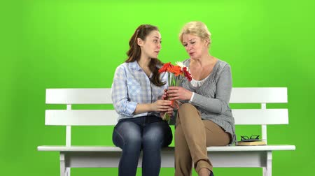 tópicos : Girl with her mother is sniffing a bouquet of flowers. Green screen Vídeos
