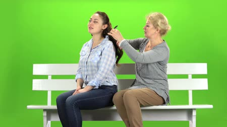 tópicos : Woman is combing her daughter. Green screen Vídeos