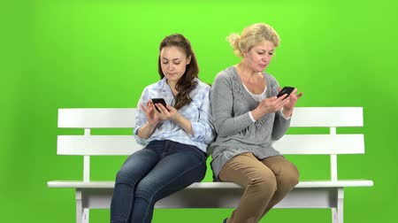 konuları : Girl and a woman are sitting on a bench and looking at the phones. Mobile dependency. Green screen Stok Video