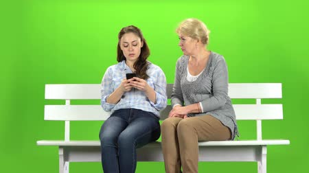 tópicos : Girl shows something in the phone to her mother. Green screen Vídeos