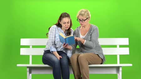 konuları : Woman and daughter is reading a book . Green screen Stok Video