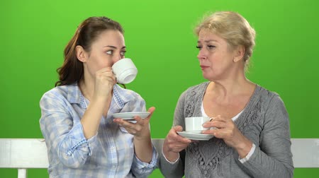 tópicos : Two women drink tea and talk. Green screen