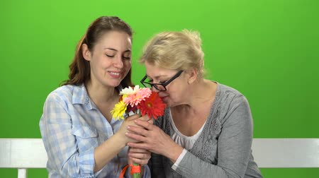 konuları : Girl with her mother is sniffing a bouquet of flowers. Green screen Stok Video