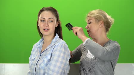 konuları : Woman is combing her daughter. Green screen Stok Video