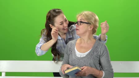 konuları : Woman sitting on a bench from behind comes daughter and makes a surprise. Green screen. Slow motion