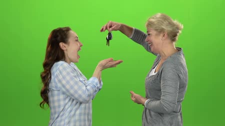 konuları : Woman gives the keys to her daughter . Green screen. Side view. Slow motion