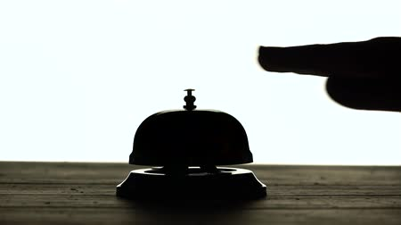 impatience : Hand presses the bell at the reception. White background. Silhouette