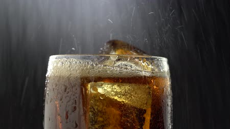 breezy : Drink pours into a glass with ice and drip drops of water. Black background. Close up Stock Footage
