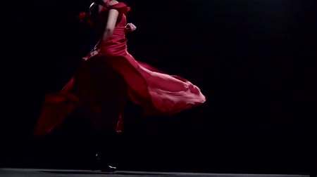 flamenco : Girl is spinning in a red dress. Black background. Slow motion Stock Footage