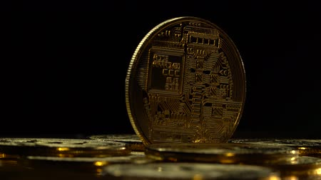 vertically : Gold coins of bitcoin peer-to-peer payment system are spinning on a black background. Close up Stock Footage
