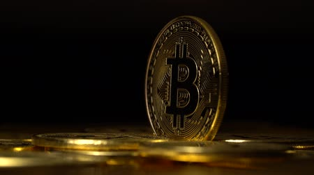 appear : Gold coins bitcoin cryptocurrencies appear and disappear on a black background. Close up Stock Footage