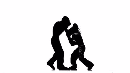 освещенный : Girl is kicking the guy they are sparring for kickboxing . Silhouette. White background Стоковые видеозаписи