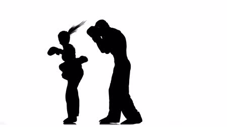 pięśc : Men with a girl boxing gloves beating in the ring . Silhouette. White background Wideo