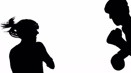 sampiyonlar : Guy with a girl preparing for a kickboxing competition. Silhouette. White background Stok Video