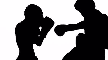бокс : Girl is kicking the guy they are sparring for kickboxing . Silhouette. White background Стоковые видеозаписи