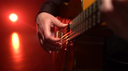 akustik : Guitar play a melody man. Close up. Light from behind Stok Video