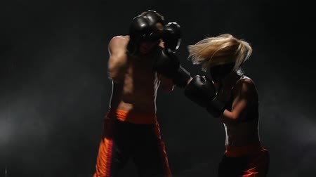 megvilágított : Sparring for kickboxing from the blow he falls to the floor. Smoke background. Slow motion