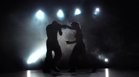 searchlight : Girl is kicking the guy they are sparring for kickboxing . Smoke background. Silhouette. Slow motion