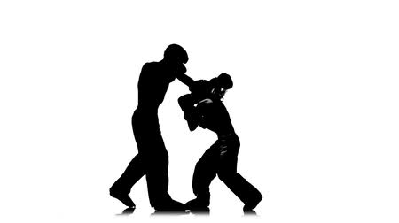 chutando : Girl is kicking the guy they are sparring for kickboxing . Silhouette. White background. Slow motion