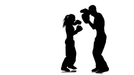 интенсивность : Kickboxing on boxing paws the girl beats feet on them the guy holds. Silhouette. White background