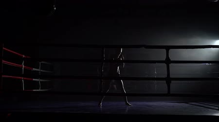 duruş : Girl trains in a dark ring kicking Stok Video