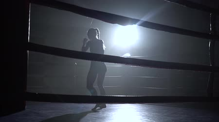 duruş : Athlete trains in the ring a dark space shines a spotlight