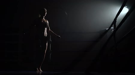 floodlight : Woman jumping rope in a dark ring. Silhouette Stock Footage