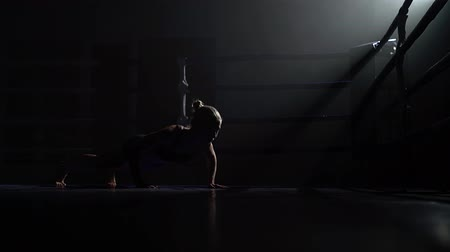 searchlight : Girl squeezes off the floor in the dark ring. Silhouette