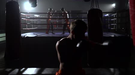 wrestler : Guy beats a pear, in the background in the ring goes sparring kickboxers Stock Footage