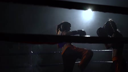 wrestler : Two girls in helmets box their hands and feet in the ring in the dark