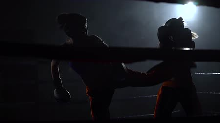 wrestler : Two women in helmets box their hands and feet in the ring in the dark