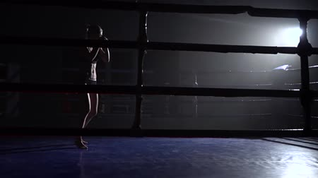 chmiel : Athlete trains in the dark ring beats her legs . Silhouette. Slow motion