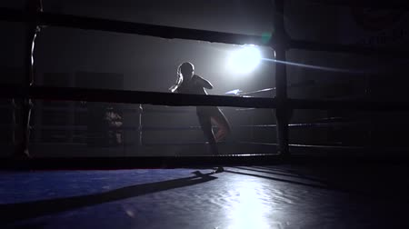 postura : Kickboxer girl in the ring punches her hands and feet . Silhouette. Slow motion