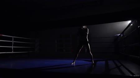 postura : Woman kickboxer preparing for the competition . Silhouette. Slow motion