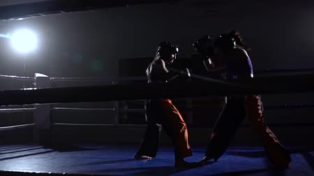 fearless : Sparring in the ring between two girls in a dark space. Slow motion