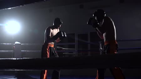 searchlight : Two guys in the ring fight in the dark . Slow motion Stock Footage