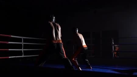 searchlight : Two guys are preparing for kickboxing competitions. Slow motion
