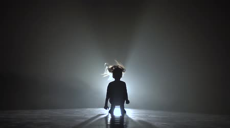 squats : Baby dances hip hop . Black smoke background. Silhouette. Light from behind. Slow motion