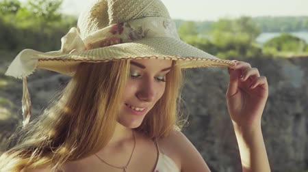 taş ocağı : Professional model posing in a hat behind a beautiful landscape . Slow motion