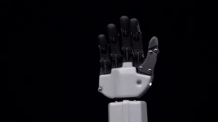 do widzenia : Robot hand close up waving bye . Black background. Close up. Slow motion