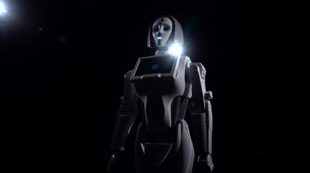 vypustit : Robot stands and looks straight. Black background