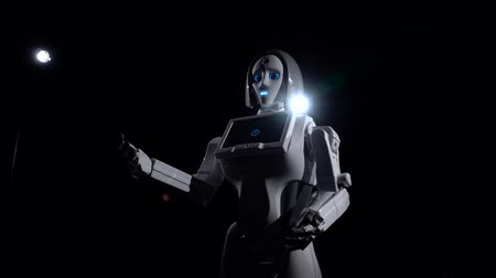 робот : Robot makes movements gesturing with his hands. Black background