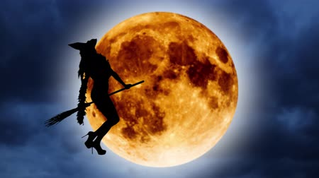 flying witch : Silhouette of a young witch flying on a broomstick against the background of the orange moon. Halloween Stock Footage