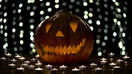 rejoice : Halloween pumpkin lights inside with flame on a black bokeh background with lighted candles Stock Footage