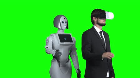 elevação : Guy with glasses of virtual reality raises his hand up and waves the robot repeats after him. Green screen