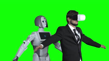 raises : Man in glasses of virtual reality picks up the robot repeats after him. Green screen